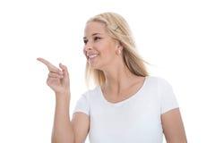 Recht lächelnder blonder Auszubildender zeigt mit ihrem Zeigefinger I Lizenzfreie Stockfotografie