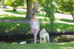 Recht lächelndes blondes Gehen mit ihrem Labrador im Park Stockbilder