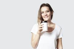 Recht lächelndes blondes Haar der jungen Frau mit Beseitigungspapiertasse kaffee, weißer Hintergrund lokalisiert Lizenzfreies Stockfoto