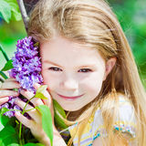 Recht lächelndes blondes kleines Mädchen mit blühender Flieder stockbilder