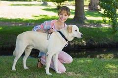 Recht lächelndes blondes Knien mit ihrem Labrador im Park Lizenzfreie Stockfotos