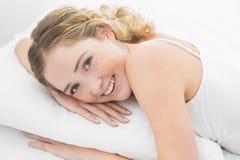Recht lächelndes blondes Lügen im Bett Lizenzfreie Stockfotos