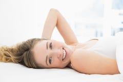 Recht lächelndes blondes Lügen im Bett, das Kamera betrachtet Lizenzfreie Stockbilder
