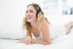 Recht lächelndes blondes Lügen im Bett, das Musik hört Stockfoto