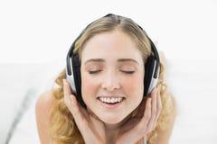 Recht lächelndes blondes Lügen im Bett, das Musik mit geschlossenen Augen hört Stockbild