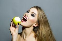 Recht lächelndes blondes Mädchen mit Apfel Lizenzfreies Stockbild