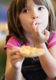 Recht lächelndes junges Mädchen, das ein Muffin isst lizenzfreies stockfoto