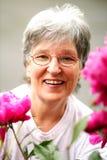Recht lachende ältere Dame durch ihre Blumen Lizenzfreies Stockfoto