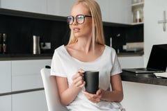 Recht nachdenkliche Dame mit der Tasse Tee sitzend in der Küche Lizenzfreies Stockbild