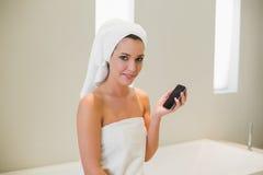 Recht natürliche braune behaarte Frau, die einen Handy verwendet Stockbilder