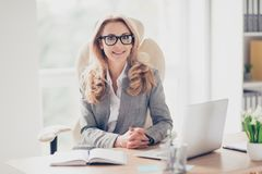 Recht nette, nette, perfekte Frau, die an ihrem Schreibtisch auf Leder sitzt Lizenzfreies Stockbild