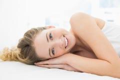 Recht nettes blondes Lügen im Bett, das Kamera betrachtet Lizenzfreie Stockfotografie