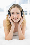 Recht nettes blondes Lügen im Bett, das Musik hört Lizenzfreie Stockfotos