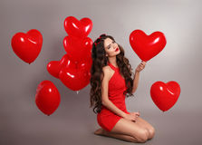 Recht nettes Brunettemädchen im Rot mit Herzen steigt im Ballon auf, Isolator aufwerfend Lizenzfreie Stockfotos