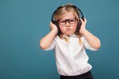 Recht nettes kleines Mädchen im weißen Hemd, Gläser, schwarze Hose und Kopfhörer Lizenzfreie Stockbilder