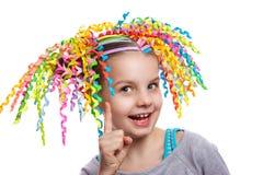 Recht nettes Mädchenporträt Kind mit bunten Strudeln des Papiers in ihrem Haarlächeln Lokalisierung auf Weiß positives menschlich Stockbild