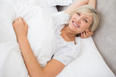 Recht reife Frau, die im Bett stillsteht Stockfotografie