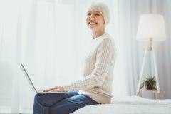 Recht reifes weibliches Arbeiten mit Laptop stockfoto