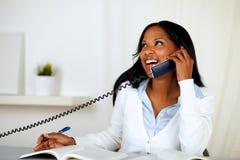Recht reizende junge Frau, die am Telefon lächelt Stockbild
