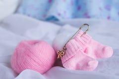 Recht rosa woolen Babysocken auf weißem Hintergrund Lizenzfreie Stockfotos