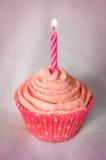 Recht rosafarbener kleiner Kuchen mit rosafarbener Kerze Lizenzfreie Stockbilder
