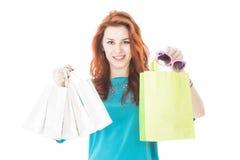 Recht rote Haarfrau, die Einkaufstaschen hält stockfoto