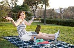 Recht rote Haarfrau, die an Laptop im Park arbeitet Stockfoto
