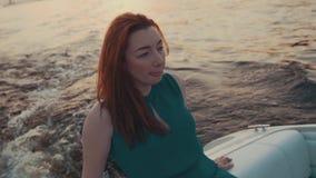 Recht rotes Haarmädchen im Türkiskleid entspannen sich auf Motorboot Kamera: Nikon F-301, AIS 28/2 stock video footage
