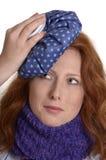 Recht rothaarige Frau, die ihren schmerzenden Kopf abkühlt stockfotografie