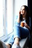 Recht ruhige junge Frau, die Handy verwendet und Lizenzfreie Stockbilder