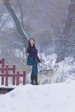 Recht ruhiger kaukasischer Brunette mit ihrem Husky Dog während eines Spaziergangs im Winter Lizenzfreie Stockbilder