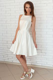 Recht süßes hübsches Mädchen in einem weißen Kleid in den hellen Modeschuhen nahe einer Backsteinmauer im Studio Stockfoto