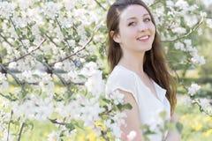 Recht süßes zartes junges Mädchen mit einem hellen Lächeln mit dem langen blonden Haar unter den blühenden Apfelbäumen Lizenzfreie Stockfotografie