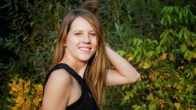 Recht schönes Mädchen im schwarzen Hemd, das im Park während des Sonnenuntergangs am warmen Tag auf grünem und gelbem Baum-Hinter Stockbilder