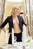 Recht schulterfreier blonder trinkender Wein im Restaurant Stockbild