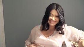 Recht schwangere Dame, die auf einem Sofa sitzt, auf einer Kamera lächelt und schaut 4K stock footage