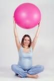 Recht schwangere Frau, die Übung mit großem gymnastischem Ball tut Lizenzfreie Stockfotos