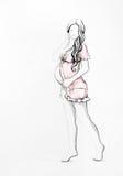 Recht schwangere Frau in einem rosafarbenen Kleid Stockbilder