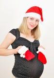 Recht schwangere Frau im Weihnachtsmann-Hut Lizenzfreies Stockbild