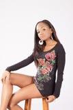 Recht schwarze Frau in der geblühten Bluse, die auf einem Schemel sitzt Stockbild