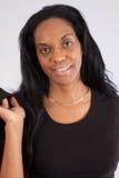 Recht schwarze Frau, die an der Kamera lächelt Lizenzfreie Stockfotografie