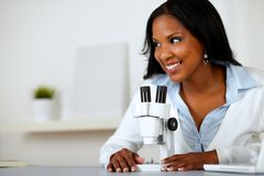 Recht schwarze Frau, die mit einem Mikroskop arbeitet Stockfotos