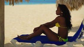 Recht schwarzes Mädchen im gelben Bikini, der auf dem Strand stillsteht stock video footage