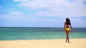 Recht schwarzes Mädchen im gelben Bikini, der zum Meer geht stock video footage