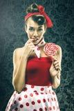 Recht sexy Frau im roten Weinlesetupfenkleid - mit Lutscher Stockfotos