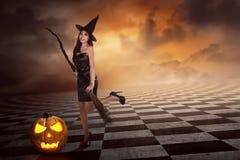 Recht sexy junge asiatische Hexenfrau mit einem Besen Stockbild