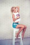 Recht sexy junge Frau mit dem blonden Haar auf Stuhl Lizenzfreies Stockbild