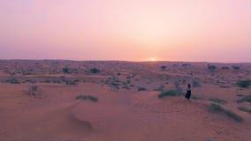 Recht sexy Mädchen tanzt in Wüste mit Sonne auf Hintergrund Glückliche Schönheit tanzt Osttanz auf Sand bei Sonnenuntergang stock video footage
