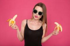 Recht sinnliche junge Frau, die zwei Bananen hält Stockbild