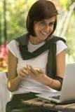 Recht smilling junge Frau, die einen Smartphone und einen Laptop verwendet lizenzfreies stockbild